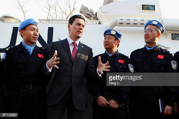 Foreign Secretary David Miliband talks with Chinese peacekeeping troops in front of an armoured personel carrier during a visit to a peacekeeping...