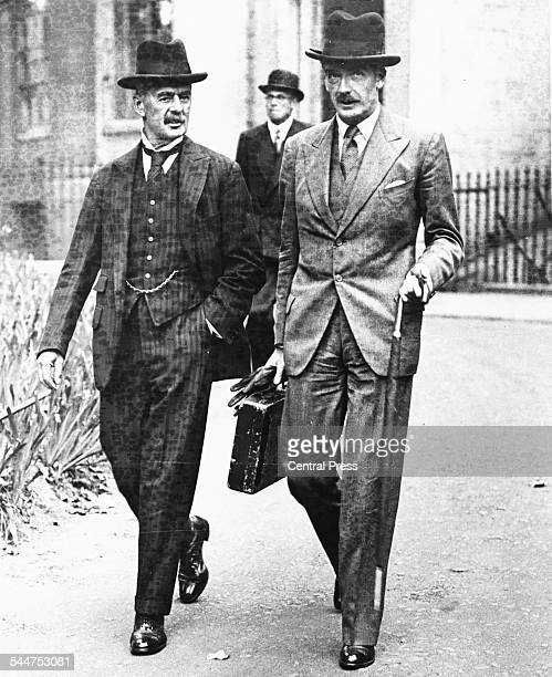 Foreign Secretary Sir Anthony Eden with Neville Chamberlain Leader of the Conservative Party both favoring a Homburg at as they walk together in...