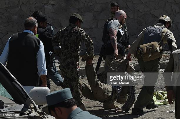 Foreign security forces carry a colleague who was a victim of a suicide attack in Kabul on May 17 2015 A powerful suicide blast struck near Kabul...
