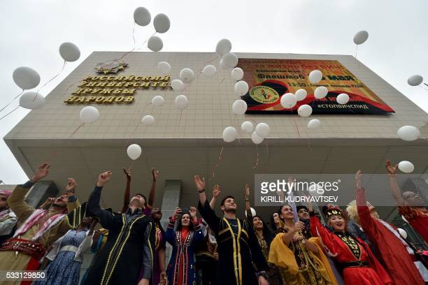 Foreign students of the University of Peoples' Friendship wearing national costumes release white balloons during a HIV/AIDS awareness rally in front...
