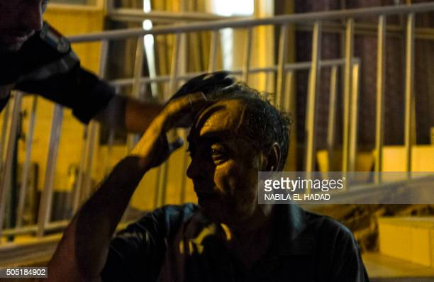 TOPSHOT A foreign survivor of the assault to the Cafe Cappuccino is assisted in Ouagadougou on January 15 2016 Sixtythree hostages including 33...