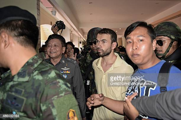 A foreign suspect in the August 17 Erawan shrine bombing identified by the ruling junta as Adem Karadag is escorted by soldiers and led by national...