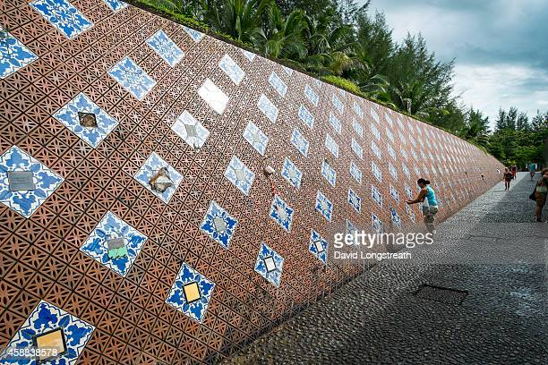 Foreign tourist and others look on as they walk along a of wall of remembrance at a tsunami memorial site This year marks the 10 anniversary of the...