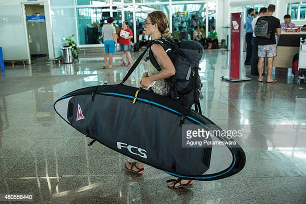 Foreign tourist carries surf boad as she arrive at Ngurah Rai international airport departure on July 13 2015 in Denpasar Bali Indonesia Bali's...