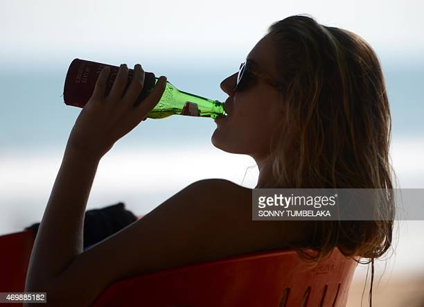 A foreign tourist drinks beer at Kuta beach near Denpasar on Indonesia's resort island of Bali on April 16 2015 Indonesia on April 16 banned small...