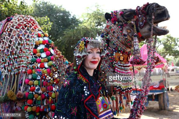 Foreign Tourist enjoying with Decorated Camel at Pushkar Camel Fair in Pushkar Rajasthan India on November 5 2019 Thousands of livestock traders from...