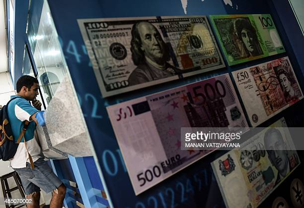 A foreign tourist inquires about exchange rates on the Malaysian ringgit at a foreign currency moneychanger in Kuala Lumpur on August 24 2015...
