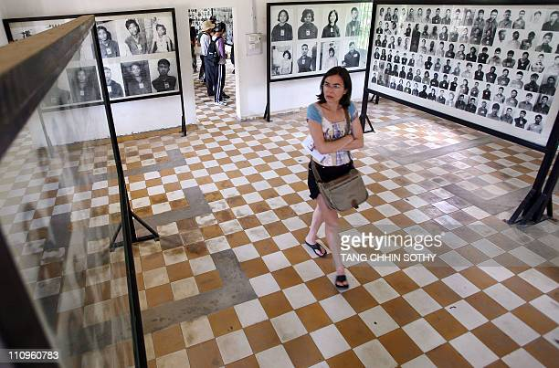 A foreign tourist looks at photos of Khmer Rouge victims on display at the Tuol Sleng genocide museum in Phnom Penh on September 2 2008 The Cambodian...