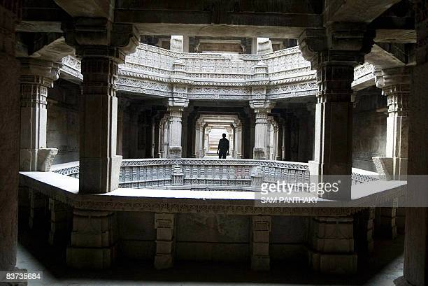 A Foreign tourist looks at stone carvings at the Adalaj Step Well at Adalaj village some 30 kms from Ahmedabad on November 18 2008 on the eve of the...