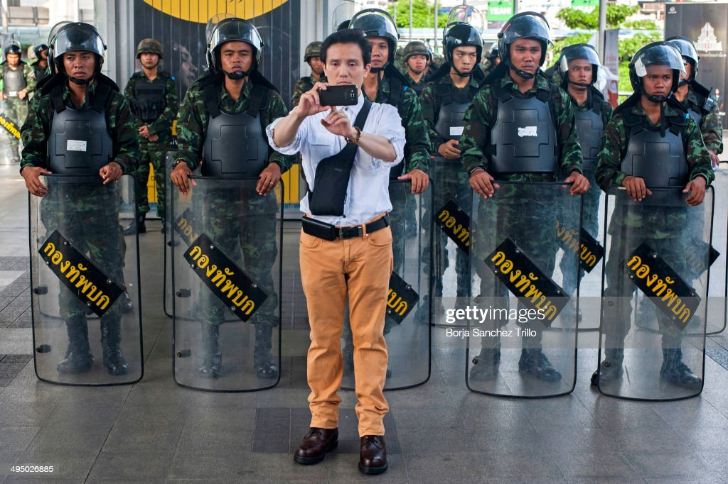 A foreign tourist makes a selfie as soldiers block the sky walk to prevent anti-coup demonstrations at the National Stadium on June 1, 2014 in Bangkok, Thailand. About 6,000 soldiers and troops were deployed by authorities in eight locations in Bangkok to prevent anti-coup demonstrations. Thailand is known as a country with a very unstable political record and is now experiencing it's 12th coup with seven attempted pervious coups.