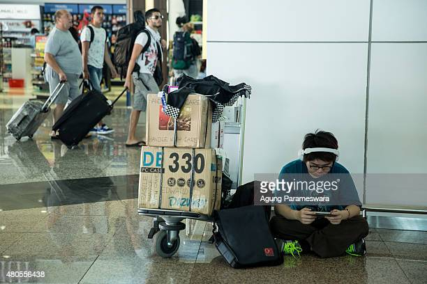 A foreign tourist plays her smart phone as he wait the flight information at Ngurah Rai international airport departure on July 13 2015 in Denpasar...