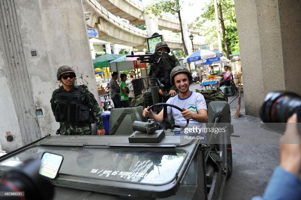 A foreign tourist poses for a photo as Thai army soldiers stand guard on a city centre street after martial law was declared on May 20, 2014 in Bangkok, Thailand. The army imposed martial law across Thailand amid a deepening political crisis that has seen six months of protests and claimed at least 28 lives.