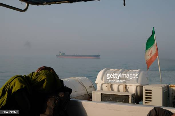 Foreign tourist rests on a passenger boat with the Iranian flag amass in the waters of the Strait of Hormuz on May 2, 2017 near Hormuz Island, Iran....
