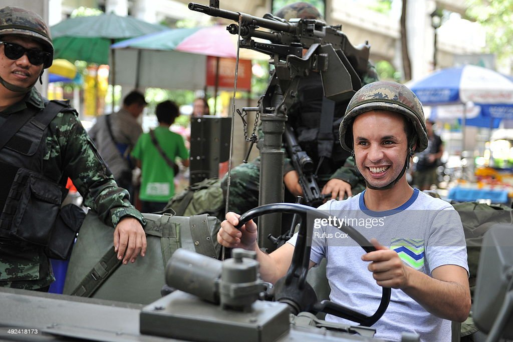 A foreign tourist sits in a Thai Army vehicle as soldiers deploy on a downtown street after martial law was declared on May 20, 2014 in Bangkok, Thailand. The army imposed martial law across Thailand amid a deepening political crisis that has seen six months of protests and claimed at least 28 lives.