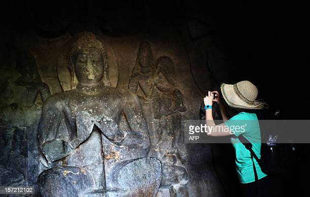 A foreign tourist takes a picture of a Buddhist carving at The Ellora Caves in the western Indian state of Maharashtra on November 16 2012 The 34...