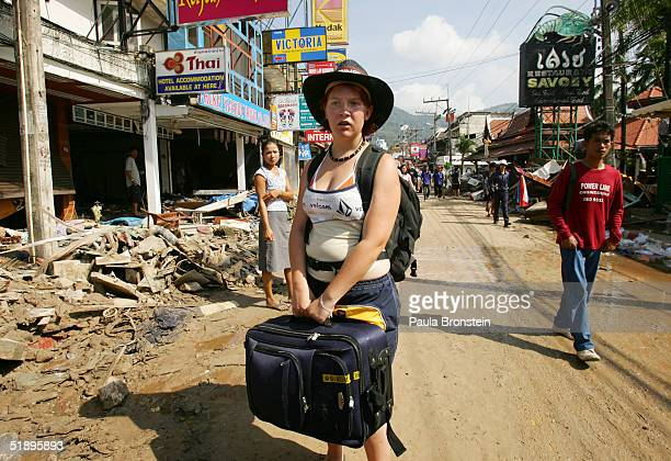 A foreign tourist waits for transportation to leave the beach area for the airport December 27 2004 in Phuket Thailand A tsunami caused by an...