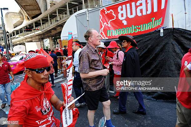 A foreign tourist walks past antigovernment protesters at the site of an ongoing rally in central Bangkok on April 8 2010 Thailand's economy is...