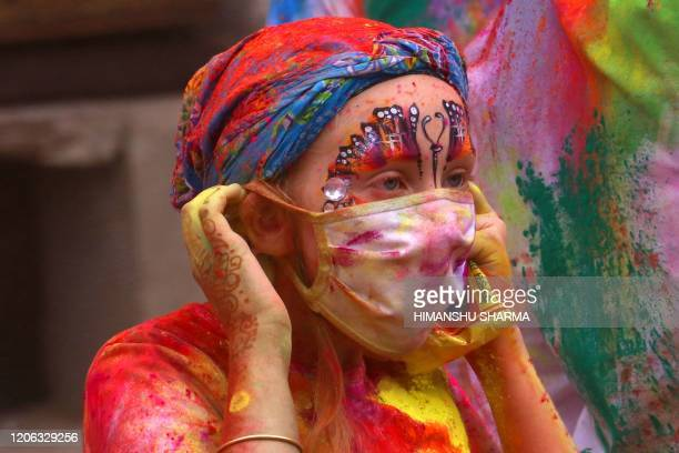 A foreign tourist wears a facemask amid fears of the spread of the COVID19 coronavirus while celebrating Holi the spring festival of colours in...
