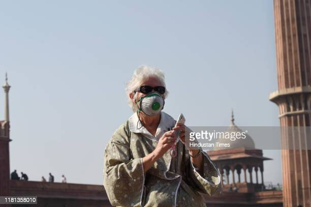 A foreign tourist wears an anti pollution protective mask on November 9 2019 in New Delhi India