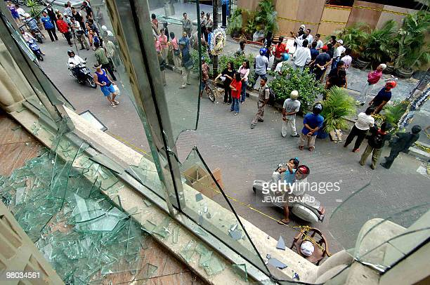 Foreign tourists and local residents pass by the the 01 October's bomb blast site in Kuta on Bali island 07 October 2005 after police removed their...