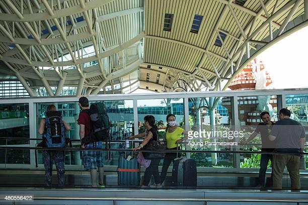 Foreign tourists arrive at Ngurah Rai International airport on July 13 2015 in Denpasar Bali IndonesiaBali's international airport reopened after...