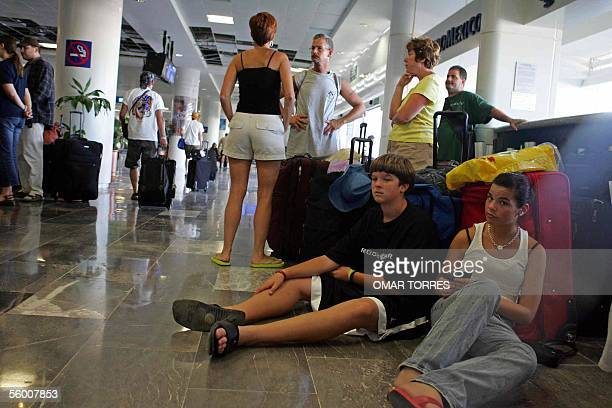 Foreign tourists await the departure of their flights at the Cancun Terminal 2 airport 25 October 2005 in the aftermath of the devastating passage of...