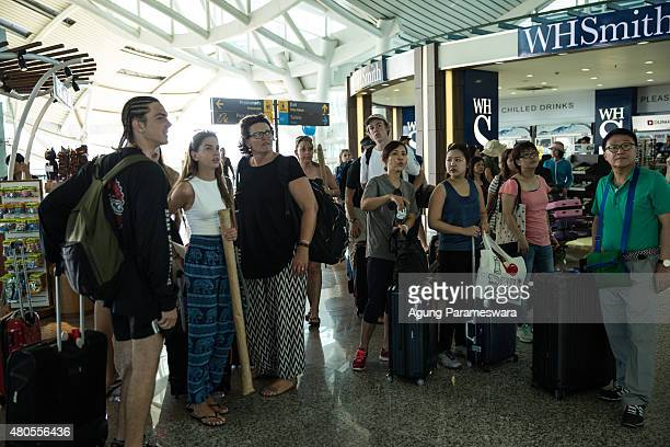 Foreign tourists check the flight information after they arrive at Ngurah Rai international airport departure on July 13 2015 in Denpasar Bali...