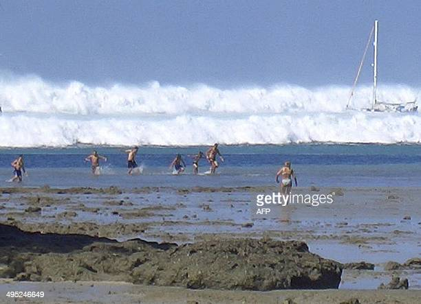 Foreign tourists far out on the sand after the water receeded react as the first of six tsunami start to roll towards Hat Rai Lay Beach near Krabi in...