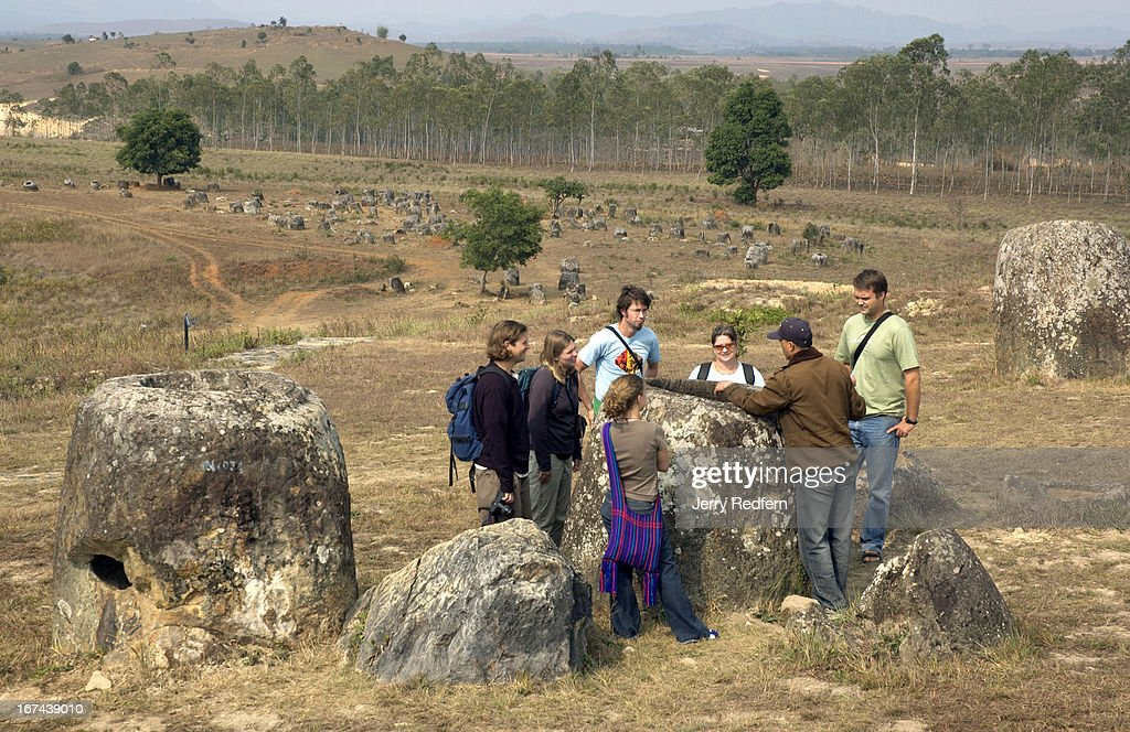 Foreign tourists listen to their guide explain the theories and history behind the Plain of Jars and surrounding Xieng Khouang province as they take a tour of Site 1 near Phonsavan..