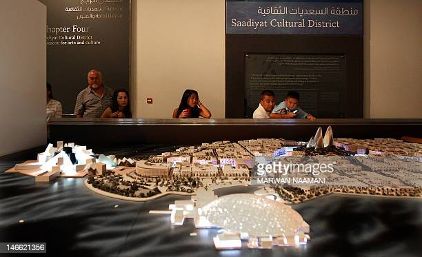 Foreign tourists look at a scale model of Saadiyat cultural district an Island off the city of Abu Dhabi on June 7 2012 which is designed by renowned...