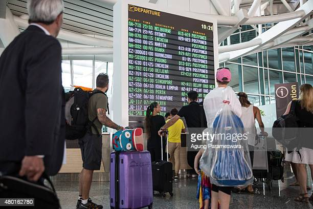 Foreign tourists look the flight schedule information board at Ngurah Rai International airport on July 10 2015 in Denpasar Bali Indonesia 277...