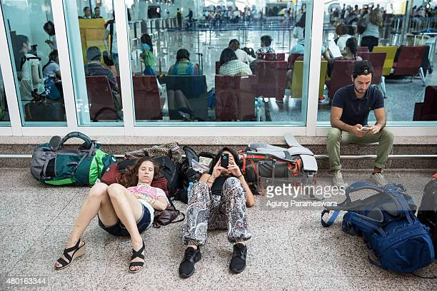 Foreign tourists play his smartphone as they wait flight schedule information at Ngurah Rai International airport on July 10 2015 in Denpasar Bali...