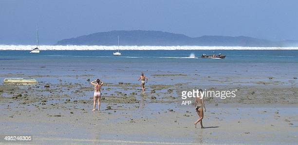 Foreign tourists react as the first of six tsunami start to roll towards Hat Rai Lay Beach near Krabi in southern Thailand 26 December 2004 The final...