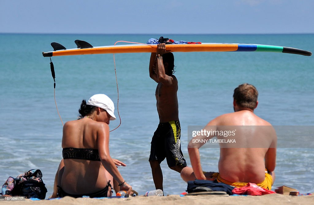 Foreign tourists relax as a man carries a surfboard at Kuta beach in Bali on April 26, 2013. According to data from the Central Statistics Agency (BPS) in February 2013, the number of foreign tourists arriving in Indonesia increased 14.5 percent to 678,400 at the beginning of the year.