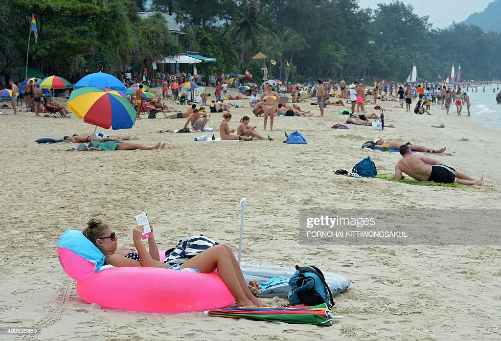 Foreign tourists relax at Patong beach in Phuket province on December 25, 2014. In the morning of December 26, 2004 a 9.3-magnitude earthquake off Indonesia's western coast generated a series of massive waves that killed more than 220,000 people across 14 countries as far apart as Indonesia, Sri Lanka and Somalia. AFP PHOTO/Pornchai KITTIWONGSAKUL