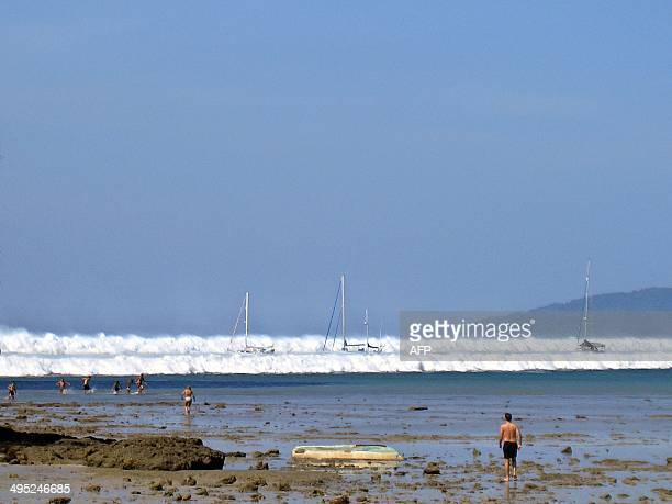 Foreign tourists run back to shore after the water receeded as the first of six tsunami start to roll towards Hat Rai Lay Beach near Krabi in...