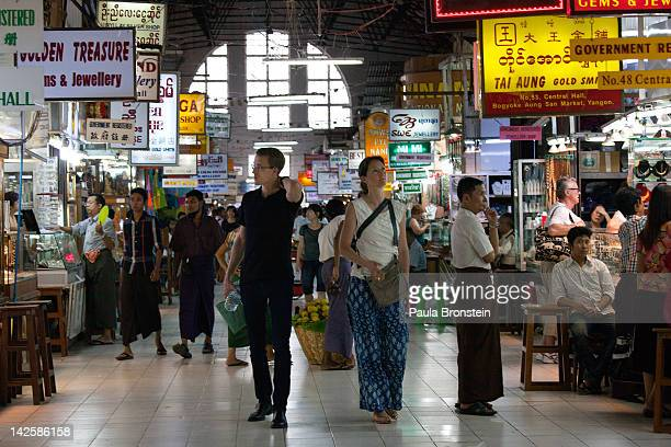 Foreign tourists shop at the Bogyoke Aung San market April 5 2012 in Yangon Myanmar With the 30 per cent increase in visas Burma has been seen as...