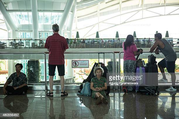 Foreign tourists sit as they wait the flight information at Ngurah Rai airport departure on July 13 2015 in Denpasar Bali Indonesia Bali's...