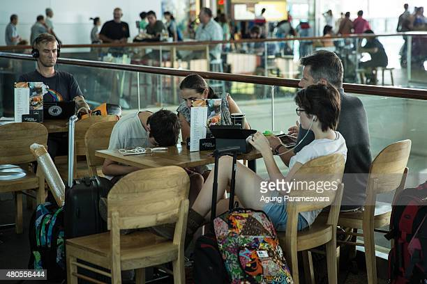 Foreign tourists sit in a cafe as they wait their flight information at Ngurah Rai international airport departure on July 13 2015 in Denpasar Bali...