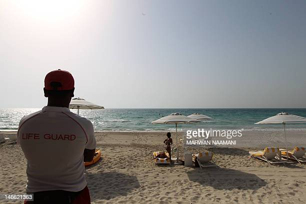 Foreign tourists sunbath along the beach at Monte Carlo Beach resort located in the Saadiyat district an Island off the city of Abu Dhabi on June 7...