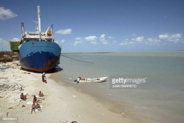 Foreign tourists sunbathe beside a vessel grounded by Hurricane Wilma 25 October 2005 at Puerto Juarez's beach north from Cancun eastern Mexico An...