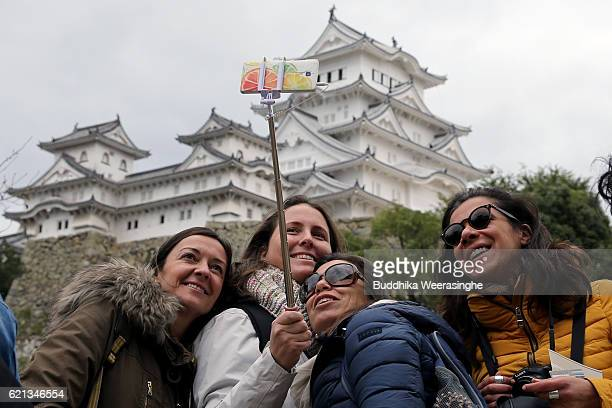 Foreign tourists take a selfie in front of the UNESCO World Heritage site Himeji Castle on November 6 2016 in Himeji Japan According to the...