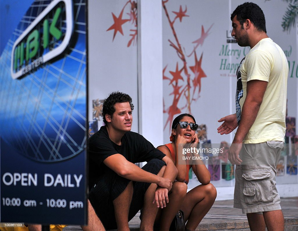 Foreign tourists take a sit in front of a shopping mall at downtown Bangkok on May 24, 2010. Thailand's prime minister said that Bangkok would get back to business on after a massive clean-up, and defended a crackdown on protest rallies that unleashed a rampage of arson and looting. AFP PHOTO / Bay ISMOYO