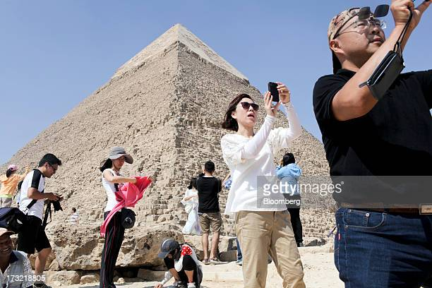 Foreign tourists take photographs of the ancient ruins inside the Giza pyramid complex in Cairo Egypt on Wednesday July 10 2013 Revenue from tourism...