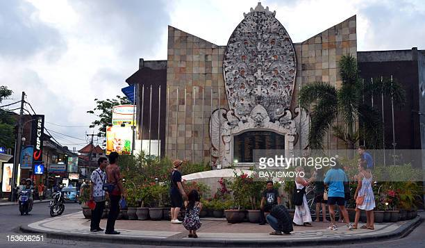 Foreign tourists take photographs of the ground zero monument in Kuta on Bali island on October 7 2012 five days before the Bali bombing anniverssary...