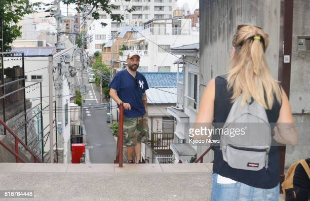 Foreign tourists take photos at a spot in Tokyo's Yotsuya district featured in the blockbuster Japanese animation film 'your name' on July 13 2017...