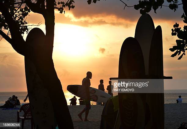Foreign tourists walk along Kuta beach during sunset in Kuta Bali province on October 7 2012 five days before the Bali bombing anniverssary on...