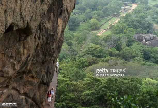 Foreign tourists walk from the 80metre fortress of Sigiriya rock in Sigiriya north central Sri Lanka on February 11 2017 The Sigiriya rock 160...