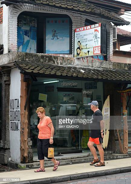 Foreign tourists walk past Australian drug trafficker Schapelle Corby's sister Mercedes Corby surfing and bikini shop in Kuta on February 8 2014...