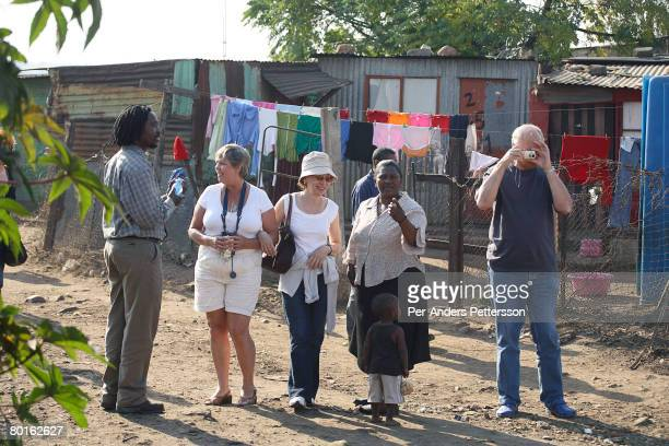 Foreign tourists walk with a tour guide in Chris Hani a poor area on May 9 2007 in Soweto South Africa The township is South Africa's largest and it...